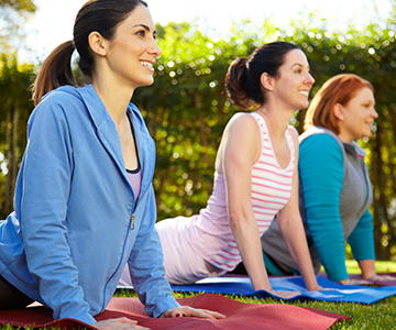 May is Women's Health Month. Picture of three women stretching.