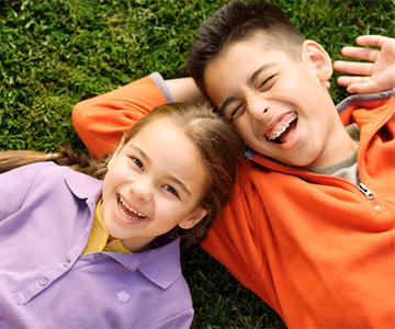 Two kids laying in the grass laughing.