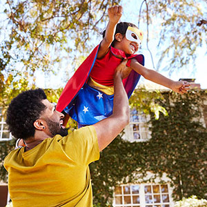 Father holding daughter dressed as a superhero