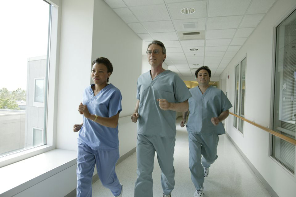 picture of three medical providers running through a hallway