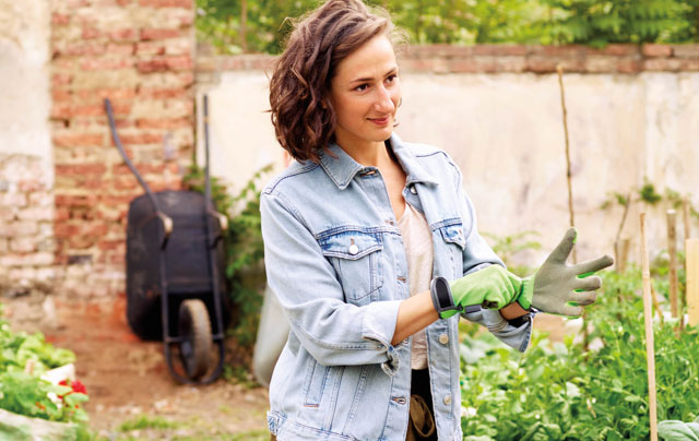 woman putting on gardening gloves