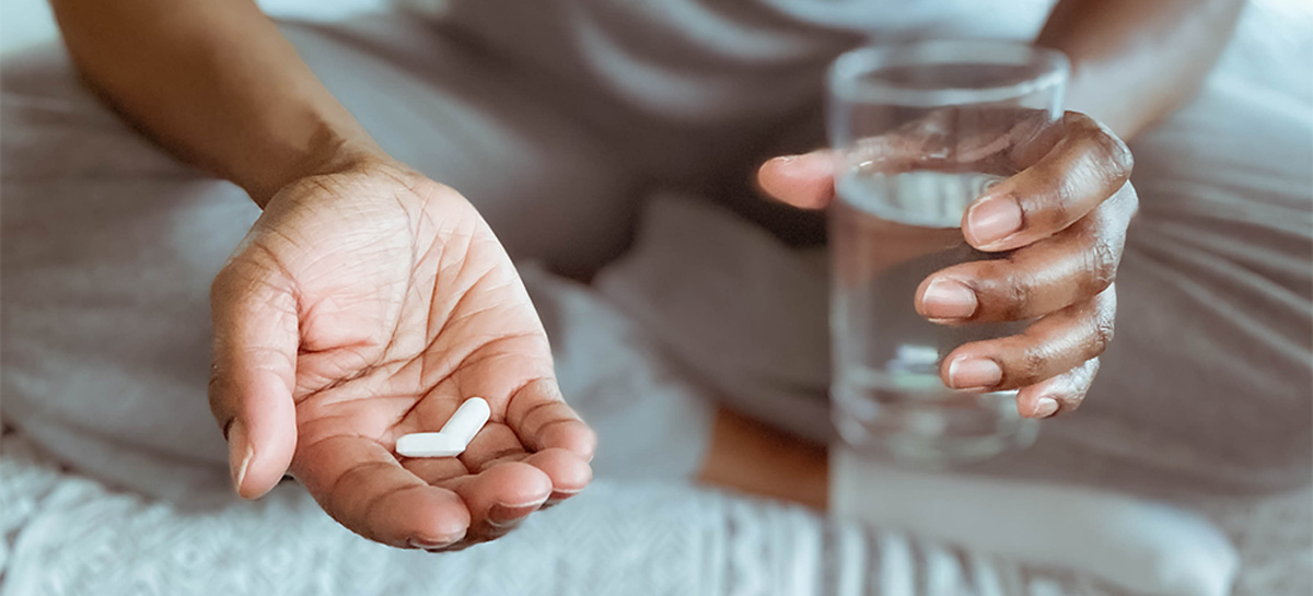 Close-up of woman sitting on bed holding pills and glass of water