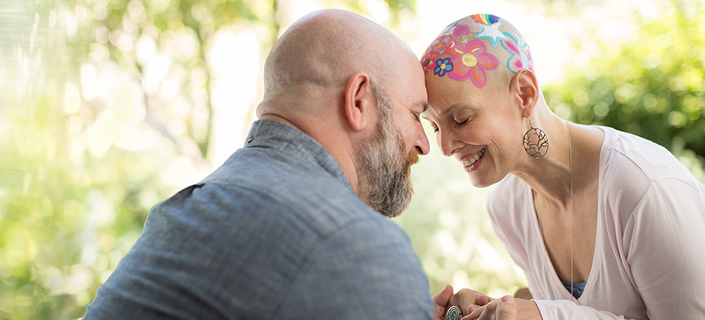 Cancer patient with head painted with her husband