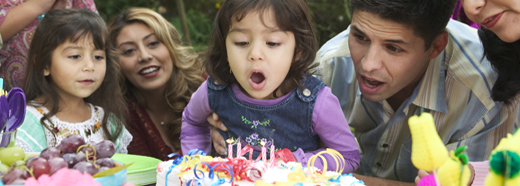 child blowing out birthday candles with family