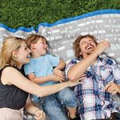 Happy family lying on blanket in meadow