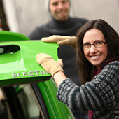 Dark haired woman standing next to green electric car