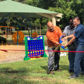 3 men cutting a ribbon for the new park opening