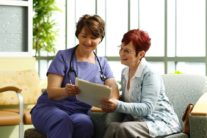 A female nurse in purple scrubs looks over paperwork with older female patient with red hair.