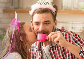 Young daughter and her father playing dress up and having a tea party.