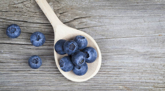 Wooden spoon holding blueberries on wood tabletop