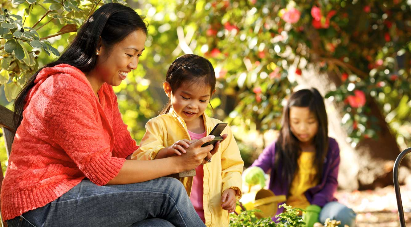 Mother and her child sitting on a garden bench looking at her smart phone.