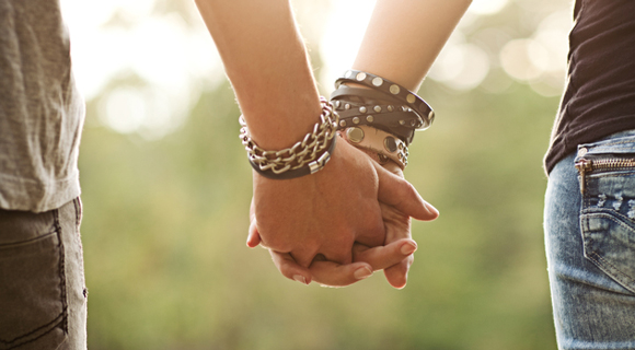 Photo of teens holding hands with many bracelets