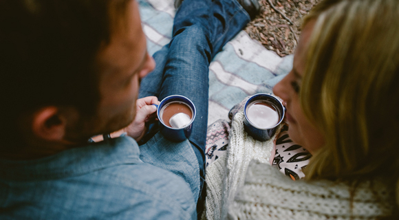 Couple gazing at each other while drinking hot chocolate