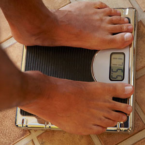 Male feet standing on bathroom scale