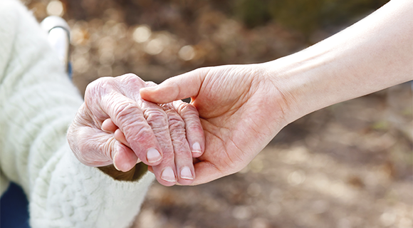 Woman holding an older person's hand