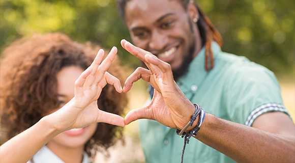 African American couple making heart shape with hands together