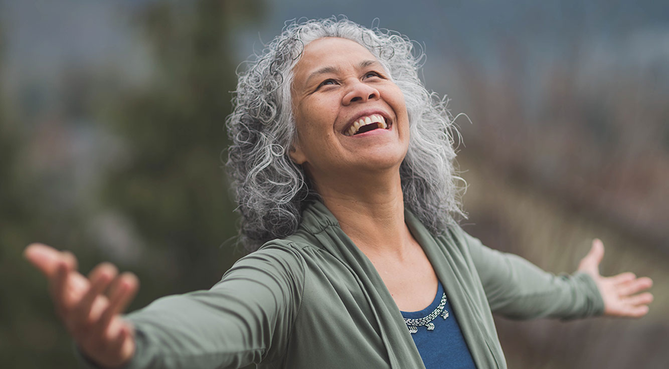 A gray-haired woman grins with open arms.