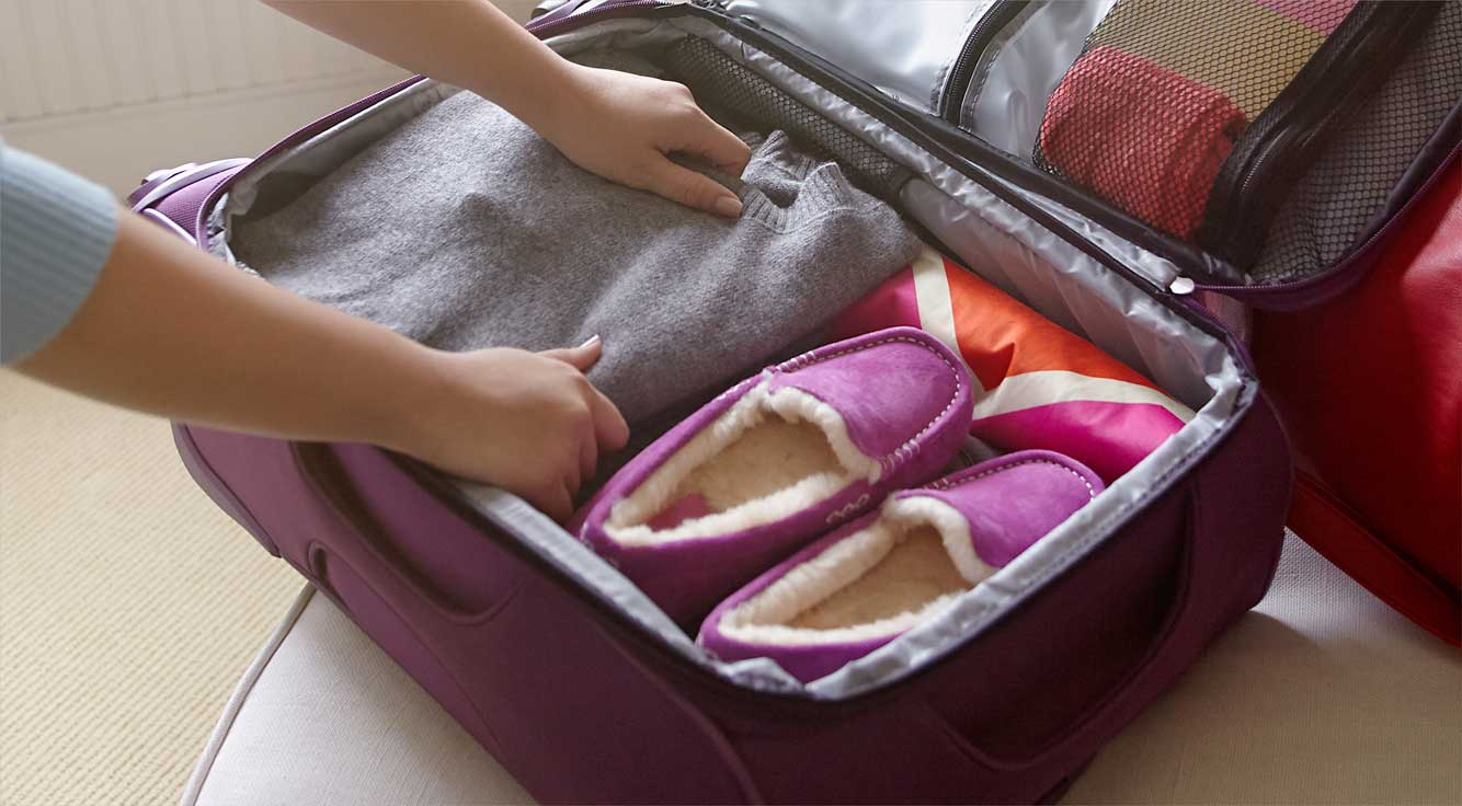 Hands pack items into a suitcase.