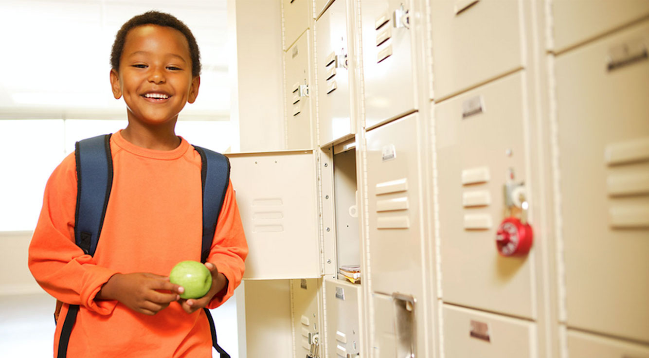 A boy smiles proudly at his school locker.