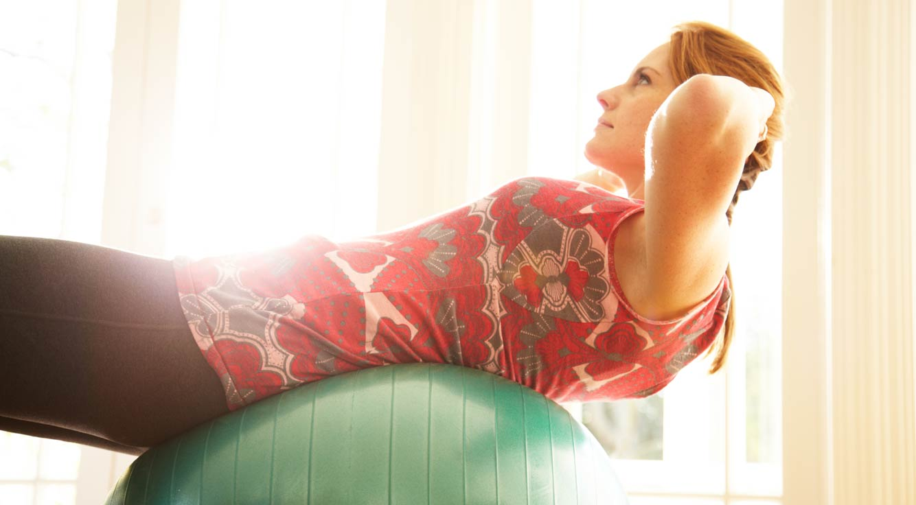 A young woman does a sit-up on a stability ball.
