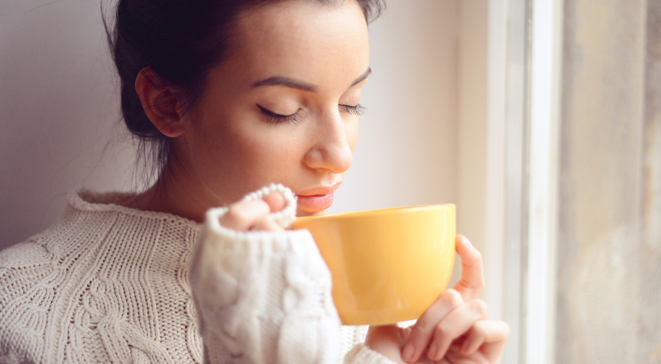 A young woman sips a cup of tea.