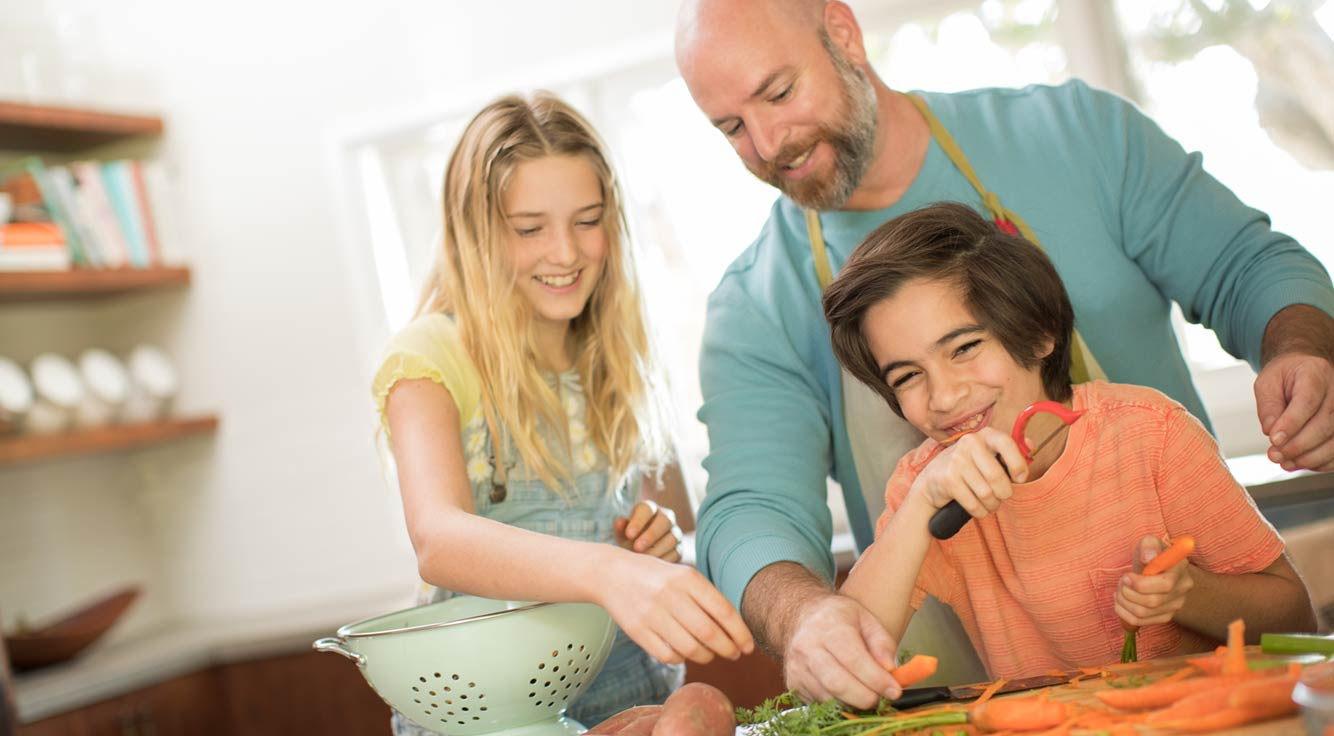 A father and his two children enjoy cooking dinner together.