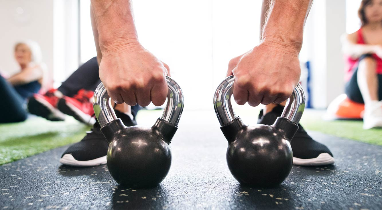 A gym-goer prepares to lift two kettlebell weights.