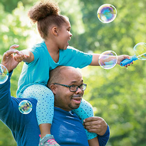 A young daughter playing with a bubble wand sits on her father's shoulders.