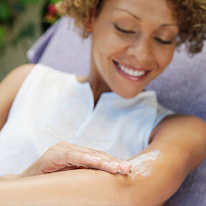 A smiling woman applies sunless tanning lotion to her arm.