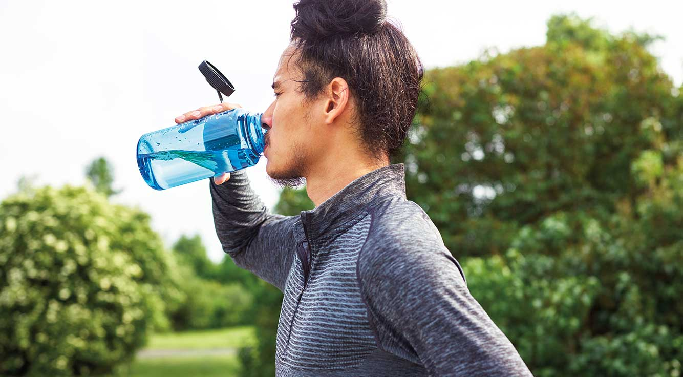A young man in workout clothes sips from a water bottle.