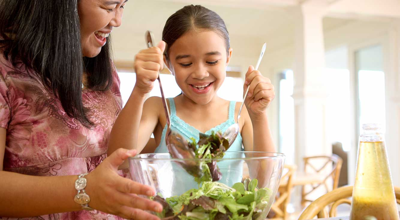 A smiling mom watches her young daughter use tongs to grab some salad from a bowl.