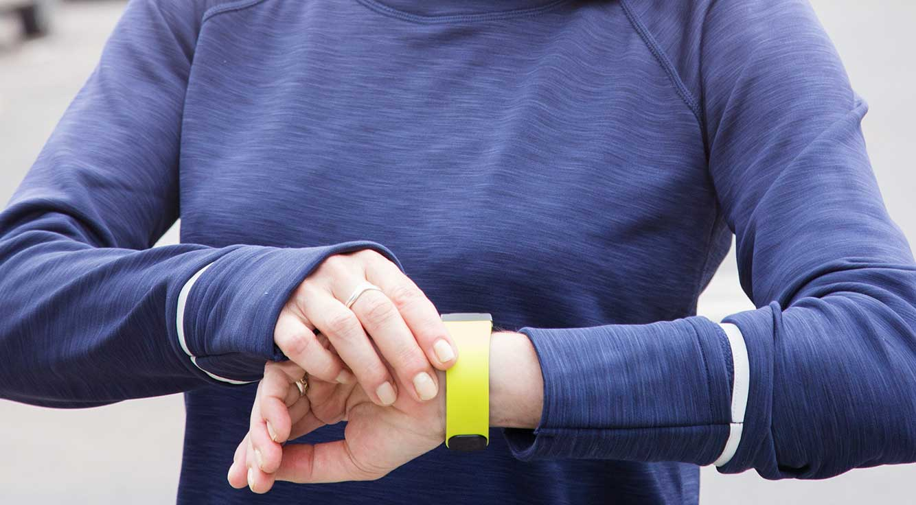 A woman in running gear checks the digital step-counter on her wrist