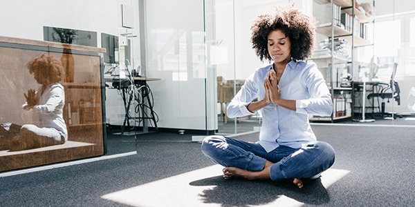 A woman sits on the floor of an office with her hands in salutation seal yoga pose.