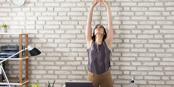 A woman stretches her arms up over her head in an upward salute yoga pose.