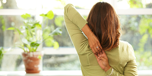 A woman clasps both hands behind her back in a yoga cow face pose.