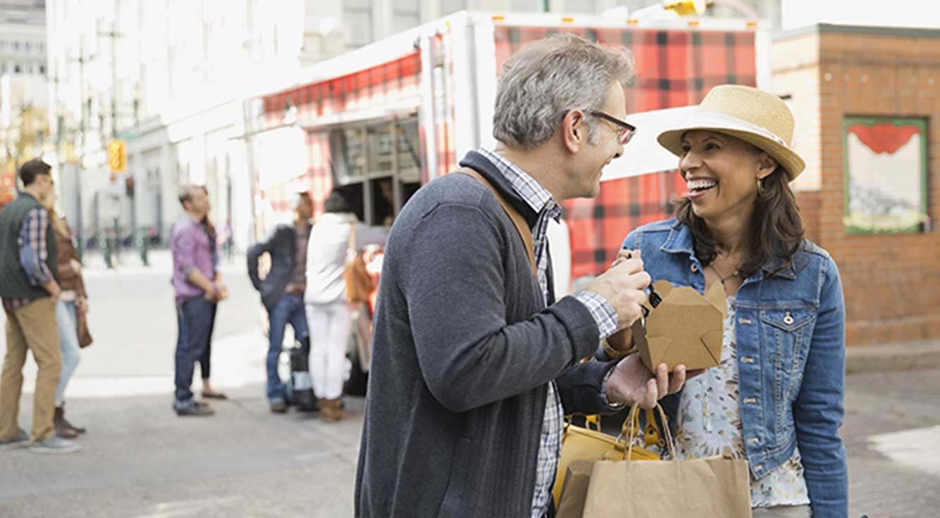A smiling middle-age couple share a meal from a food truck on a city street