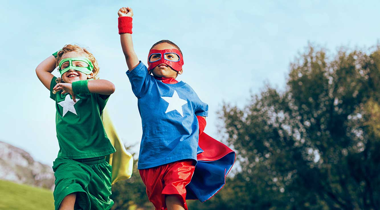 Two children dressed as superheroes play together outside.