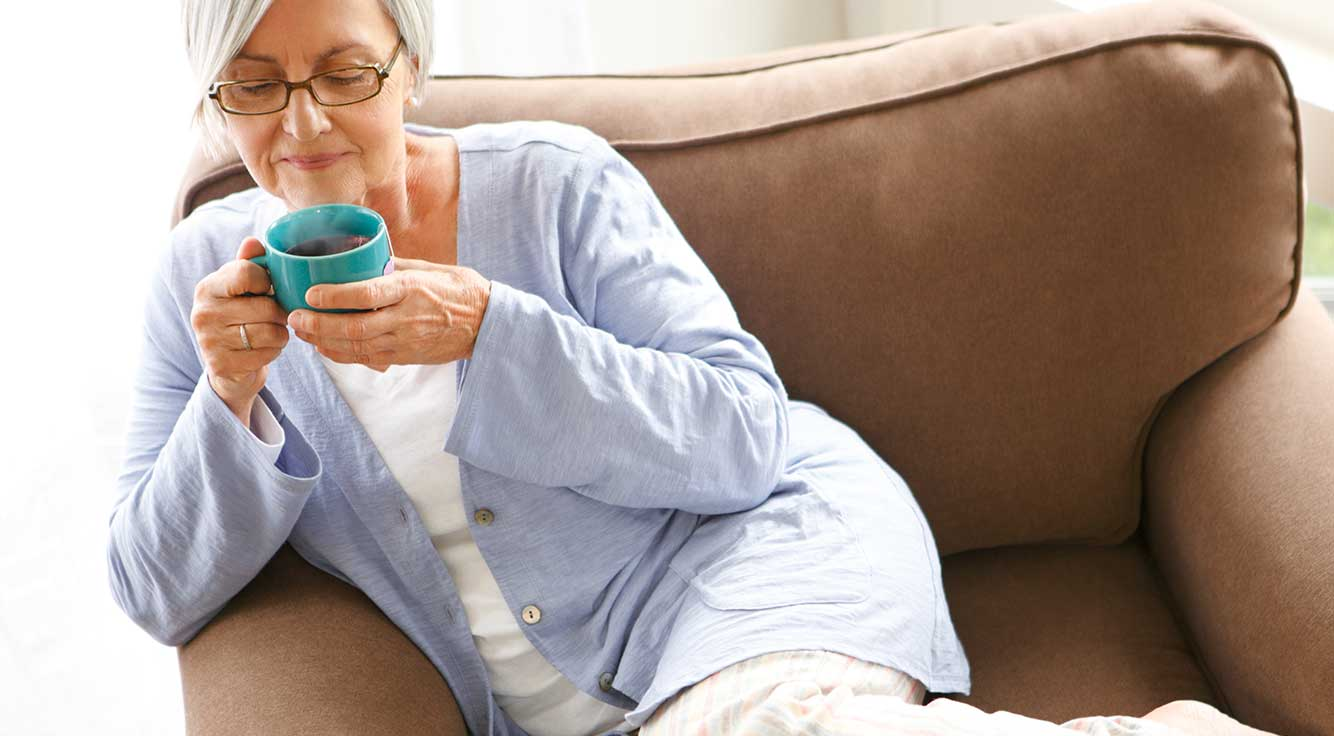 An older woman enjoys a cup of tea on the couch.