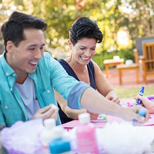A smiling woman enjoys craft time with two friends.