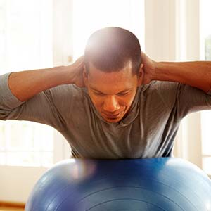 A man working out at home using a yoga ball