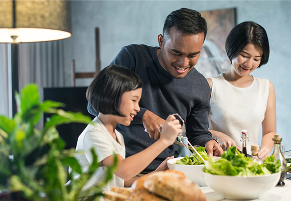 A smiling family makes salad together.