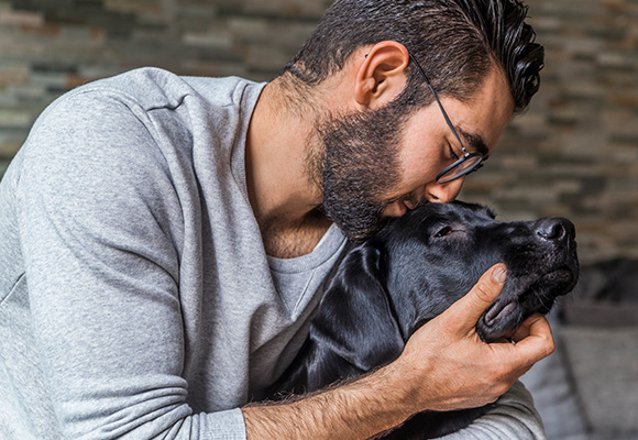 Man smiles as he cuddles his dog.