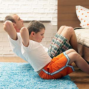 A father and son do sit-ups indoors.