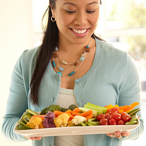 Smiling woman holds plate of colorful vegetables