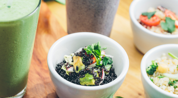 Bowls of grains and vegetables with glasses of smoothies