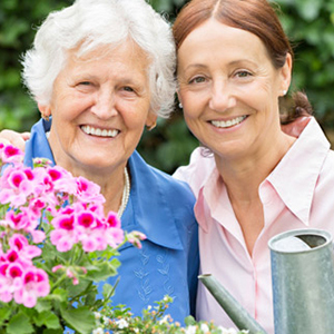 Two women gardening and smiling
