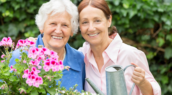 Senior woman and middle-aged woman gardening and smiling