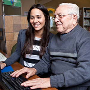 Young woman helping older man use computer.