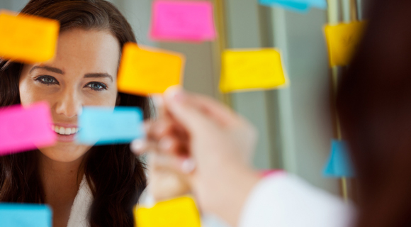 Woman smiling in mirror with sticky notes on it