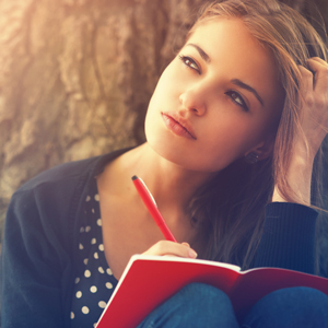 Young woman writing in journal in deep thought